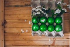 Gröna påskägg i den pappers- behållaren på träbakgrunden med en filial av den körsbärsröda blomningen royaltyfri bild