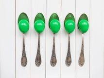 Gröna påskägg i gamla skedar Royaltyfri Fotografi