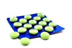 Gröna preventivpillerar i blått förpacka royaltyfri fotografi