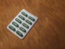 Gröna preventivpillerar i den vita blåsapacken på den gamla skrapade träsuen royaltyfri foto