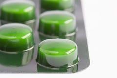 Gröna preventivpillerar i en blåsapacke arkivfoto