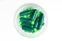 Gröna preventivpillerar och kapslar i en flaska Royaltyfri Fotografi