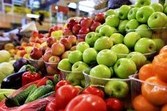 Gröna, röda gula äpplen, frukter och grönsaker som är till salu i marknaden royaltyfri foto