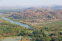 Gröna risfält, gömma i handflatan och floden Tungabhadra i byn av Hampi Palmträd solen, risfält Tropiskt exotiskt royaltyfri bild