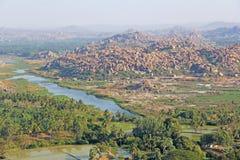 Gröna risfält, gömma i handflatan och floden Tungabhadra i byn av Hampi Palmträd solen, risfält Tropiskt exotiskt royaltyfria foton