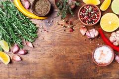 Gröna rosmarin och blandade kryddor på träbästa sikt för köksbord Ingredienser för matlagning många bakgrundsklimpmat meat mycket royaltyfri bild