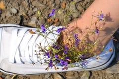 Gröna små blommor för lilor som sätts in i vita gymnastikskor med ett anseende för fot för flicka` s på en sten royaltyfria foton