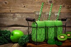 Gröna smoothies i flaskor i en tappningkorg mot lantligt trä arkivbild