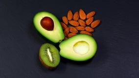 Gröna sortimentgrönsaker och frukter, avokadon, kiwin och mandlar, muttrar på en skiffer stiger ombord, begreppet av sunt äta, ko arkivfoton