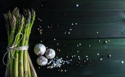 Gröna sparriers med salt, vitlök och peppar blandar på mörk bakgrund, bästa sikt Royaltyfri Fotografi