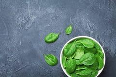 Gröna spenatsidor i bunke på den svarta tabellen från över Organisk mat royaltyfri fotografi