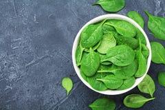 Gröna spenatsidor med vatten tappar i bunke på bästa sikt för tabell Organisk mat arkivbilder