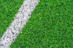 Gröna syntetiska grässportar field med den vita linjen Arkivfoton
