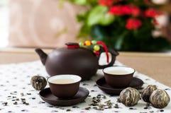 Gröna teblad och uppsättningen av uppsättningkoppar och te för japansk stil lägger in Arkivfoto
