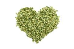 Gröna torkade delade ärtor i en hjärtaform Royaltyfri Bild