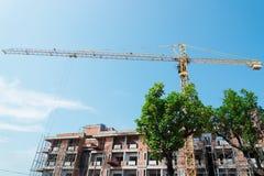 Gröna träd står framme av kran- och byggnadskonstruktionsplats arkivfoton