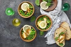Gröna unga ärtor, osthaloumi, citron orange sallad med skivor av bröd Top beskådar fotografering för bildbyråer