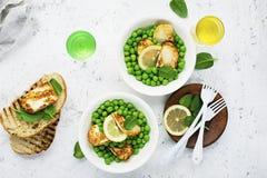Gröna unga ärtor, osthaloumi, citron orange sallad med skivor av bröd Top beskådar royaltyfri bild