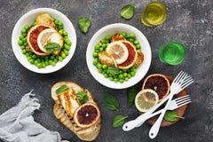 Gröna unga ärtor, osthaloumi, citron orange sallad med skivor av bröd Top beskådar arkivbild