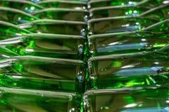Gröna vinflaskor fyllde med staplat vitt vin arkivbild