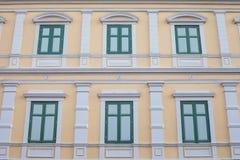 Gröna Windows på den gula tappningväggen Arkivbilder