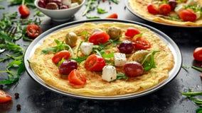 Grönsakäggomelett med tomater, lös raket, grekisk ost, oliv i en platta Sund mat för morgonfrukost arkivbilder