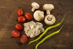 Grönsak: Den bästa sikten av ostron- och knappchampinjoner med rött behandla som ett barn tomater på brun träbakgrund Arkivbilder