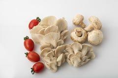 Grönsak: Den bästa sikten av ostron- och knappchampinjoner med rött behandla som ett barn tomater på vit bakgrund Arkivbilder