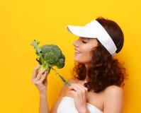 Grönsak för broccoli för tugga för ung kvinna stor ny grön i den vita hatten royaltyfri foto