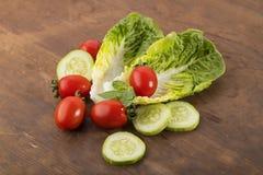 Grönsak: Nya gröna Romaine Lettuce med behandla som ett barn tomater, mintkaramellsidor och gurkaskivor på brun träbakgrund Royaltyfri Foto