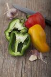 Grönsak på träyttersida med kniven Arkivbilder