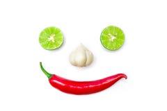 Grönsak som ler framsidan från peppar, vitlök och limefrukt för röd chili på vit bakgrund royaltyfri foto
