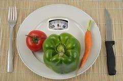 Grönsaken bantar på en vägningsskala royaltyfri bild