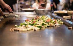 Grönsaken steker under omrörning Arkivbild