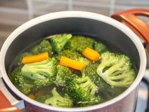 Grönsaker av broccoli, i att koka krukor broccoli som kokar på ugnen i köket royaltyfria foton