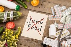 Grönsaker eller preventivpillerar Papper med text & x22; INGET skräp Food& x22; , stetoskop royaltyfri fotografi