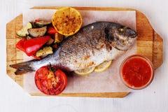 Grönsaker för doradoen för den vita fisken isolerade hela, havre, bräde för tomatcitronpeppar bakgrundsseabassen Royaltyfri Fotografi