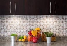Grönsaker, frukter och örtar i ett kök med hemtrevlig belysning Arkivfoto
