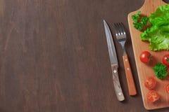 Grönsaker, gaffel och kniv, skärbräda på en mörk träbackg Fotografering för Bildbyråer