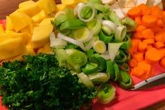 Grönsaker klippte på en skärbräda arkivfoto