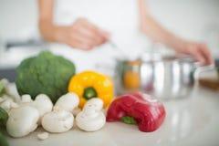 Grönsaker med den suddiga kvinnan som förbereder mat i kök arkivfoton