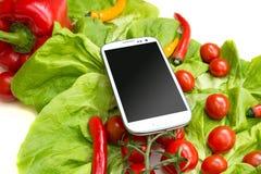 Grönsaker och en Smartphone Arkivbild