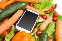 Grönsaker och en Smartphone Arkivfoto