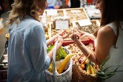 Grönsaker och frukter för vänner för unga kvinnor skälla på marknaden royaltyfri foto