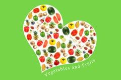 Grönsaker och frukter på en vit hjärta. arkivfoton