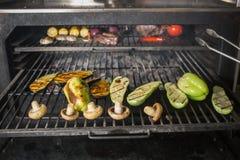 Grönsaker och kött på gallret på varma kol med rök royaltyfri bild