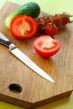 Grönsaker och kniv på träskärbräda Royaltyfria Foton