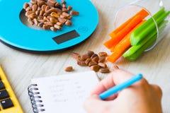Grönsaker och muttrar på vågen Räkna för kalori royaltyfri foto