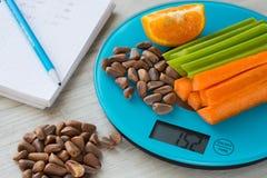 Grönsaker och muttrar på vågen Räkna för kalori arkivbild