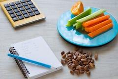 Grönsaker och muttrar på vågen Räkna för kalori arkivbilder